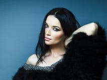Giovane ragazza castana graziosa con la posa di trucco di modo elegante in pelliccia con gioielli su fondo blu, stile di vita immagini stock