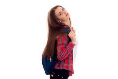Giovane ragazza castana stanca dello studente con lo zaino blu che posa e che esamina la macchina fotografica isolata su fondo bi Fotografia Stock Libera da Diritti