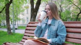 Giovane ragazza castana su un caffè bevente e sulla lettura del banco del libro stock footage