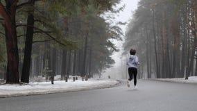 Giovane ragazza caucasica attraente che corre nel parco nevoso nell'inverno Colpo statico posteriore stock footage