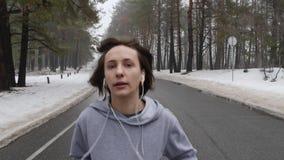 Giovane ragazza caucasica attraente che corre nel parco nevoso nell'inverno con le cuffie Aperto vicino segue il colpo stock footage