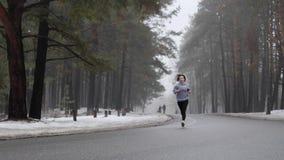 Giovane ragazza caucasica attraente che corre nel parco nevoso nell'inverno con le cuffie Front Static Shot Movimento lento archivi video