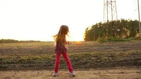 Giovane ragazza caucasica che salta e che sembra sideway Ballando nel tramonto rurale di autunno di scena del campo Slowmo archivi video