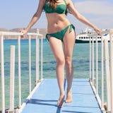 Giovane ragazza caucasica in un costume da bagno verde sul pilastro blu, dal mare ionico blu del fondo, Balos, Grecia fotografie stock libere da diritti