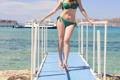 Giovane ragazza caucasica in un costume da bagno verde sul pilastro blu, dal mare ionico blu del fondo, Balos, Grecia fotografia stock