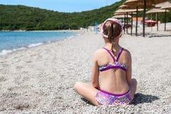 Giovane ragazza caucasica in vestito di nuotata che si siede sulla spiaggia sabbiosa vicino alla costa di mare, retrovisione, cop Fotografia Stock