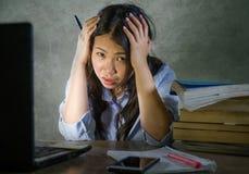 Giovane ragazza cinese asiatica depressa e sollecitata dello studente che lavora con il mucchio del libro e del computer portatil fotografie stock
