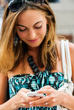 Giovane ragazza d'avanguardia (21) che passa in rassegna Internet con il suo telefono cellulare Immagini Stock Libere da Diritti
