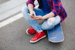 Giovane ragazza dei pantaloni a vita bassa che chiacchiera sul suo telefono Immagine Stock