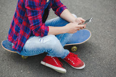 Giovane ragazza dei pantaloni a vita bassa che si siede al parco del pattino e che chiacchiera sul suo telefono Fotografie Stock