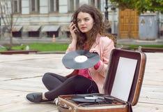 Giovane ragazza dei pantaloni a vita bassa con vecchia musica d'ascolto d'annata dei dischi di vinile nel parco della città Immagine Stock Libera da Diritti