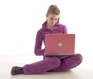 Giovane ragazza del brunette che per mezzo del computer portatile fotografia stock libera da diritti