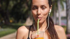 Giovane ragazza del corridore di corsa mista che beve succo d'arancia fresco dopo l'allenamento nel parco della città 4k, movimen archivi video