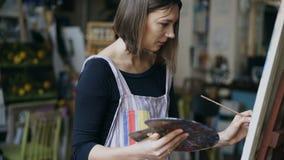 Giovane ragazza del pittore nell'immagine di natura morta della pittura del grembiule su tela in classe arte Immagine Stock