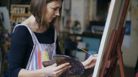 Giovane ragazza del pittore nell'immagine di natura morta della pittura del grembiule su tela in classe arte Fotografia Stock Libera da Diritti