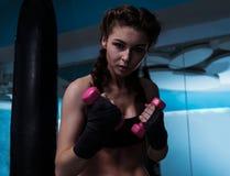 Giovane ragazza del pugile del combattente con la fasciatura della mano nell'addestramento con muto Fotografia Stock