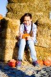 Giovane ragazza dell'adolescente che si siede sulla paglia con i pumkins sul mercato dell'azienda agricola Famiglia che celebra r fotografia stock