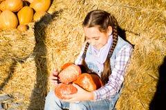 Giovane ragazza dell'adolescente che si siede sulla paglia con i pumkins sul mercato dell'azienda agricola Famiglia che celebra r fotografia stock libera da diritti