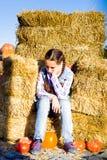Giovane ragazza dell'adolescente che si siede sulla paglia con i pumkins sul mercato dell'azienda agricola Famiglia che celebra r fotografie stock libere da diritti