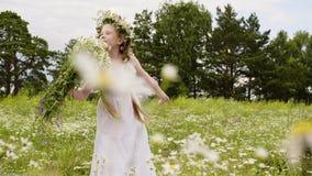 Giovane ragazza dell'adolescente nel mazzo dei fiori di fiuto della corona sul campo di fioritura Modello di moda che posa con i  archivi video