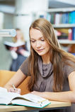 Giovane ragazza dell'allievo che lavora con il libro in libreria Fotografia Stock Libera da Diritti
