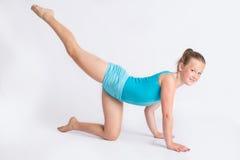 Giovane ragazza della ginnasta nella posa di allungamento della gamba Fotografie Stock