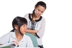 Giovane ragazza della scuola che studia con l'insegnante X Immagine Stock