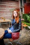 Giovane ragazza della testarossa in cappello in un caffè a Amsterdam Fotografia Stock Libera da Diritti
