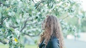 Giovane ragazza della testarossa nei fiori di primavera archivi video