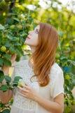 Giovane ragazza della testarossa nel giardino di melo fotografie stock