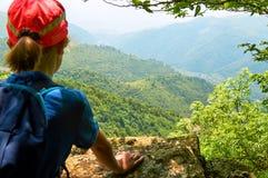 Giovane ragazza della viandante che gode di bella vista dall'alta scogliera in montagne armene di estate Fotografie Stock