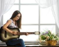 Giovane ragazza dello studente che gioca musica sulla chitarra Fotografie Stock