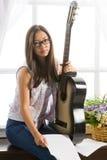 Giovane ragazza dello studente che gioca musica sulla chitarra Fotografie Stock Libere da Diritti