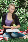 Giovane ragazza dello studente che legge un libro in parco Immagine Stock