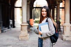 Giovane ragazza dello studente di bellezza con i taccuini all'aperto la bevanda dell'università un la tazza di caffè Fotografia Stock Libera da Diritti