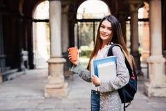 Giovane ragazza dello studente di bellezza con i taccuini all'aperto la bevanda dell'università un la tazza di caffè Immagine Stock