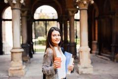 Giovane ragazza dello studente di bellezza con i taccuini all'aperto la bevanda dell'università un la tazza di caffè Fotografie Stock Libere da Diritti