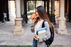 Giovane ragazza dello studente di bellezza con i taccuini all'aperto la bevanda dell'università un la tazza di caffè Immagini Stock Libere da Diritti
