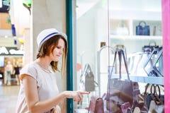 Giovane ragazza di dubbio che esamina la finestra del negozio con le scarpe e le borse nel centro commerciale Cliente vendite Cen immagini stock libere da diritti
