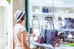 Giovane ragazza di dubbio che esamina la finestra del negozio con le scarpe e le borse nel centro commerciale Cliente vendite Cen fotografia stock