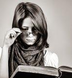Giovane ragazza di dubbio in vetri con il vecchio libro fotografie stock libere da diritti