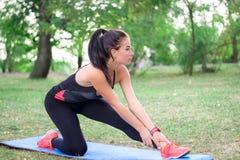 Giovane ragazza di forma fisica che allunga le gambe durante l'allenamento di addestramento Immagini Stock Libere da Diritti