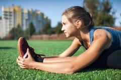 Giovane ragazza di forma fisica che fa allungamento nel tramonto Primo piano del campo di football americano Immagine Stock Libera da Diritti