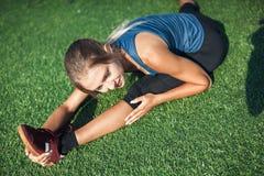 Giovane ragazza di forma fisica che fa allungamento nel tramonto Primo piano del campo di football americano Immagine Stock