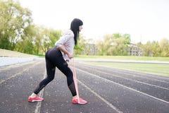 Giovane ragazza di forma fisica che fa allungamento sullo stadio Attivit? di sport di estate Fondo verde dello stadio con lo spaz fotografie stock