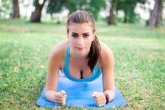 Giovane ragazza di forma fisica che fa esercizio della plancia durante l'allenamento Immagine Stock