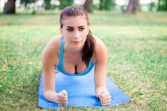 Giovane ragazza di forma fisica che fa esercizio della plancia durante l'allenamento di addestramento Immagine Stock