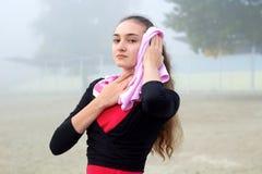 Giovane ragazza di forma fisica con l'asciugamano durante il outd della rottura di allenamento di addestramento Fotografia Stock