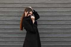 Giovane ragazza di modello alla moda in coperture nere del cappotto immagini stock