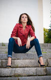 Giovane ragazza di modo che si siede sulle scale Fotografie Stock Libere da Diritti